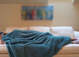 Bărbat care suferă de insomnie și a adormit pe canapea