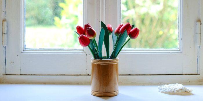 vaza din lemn cu lalele rosii asezata pe pervaz in fata unei fereastre