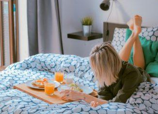 femeie care ia micul dejun in pat