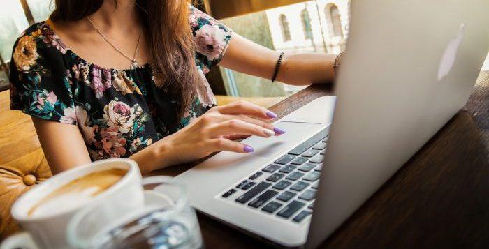 femeie care lureaza la laptop la birou