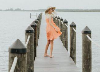 femeie care se plimba pe un dig de lemn