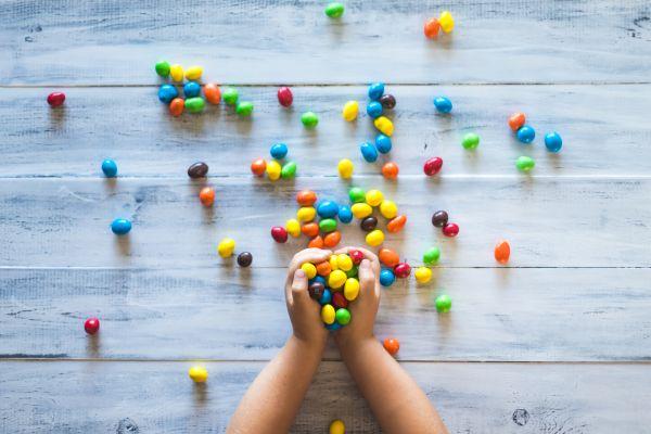 copil care tine in maini multe bomboane colorate