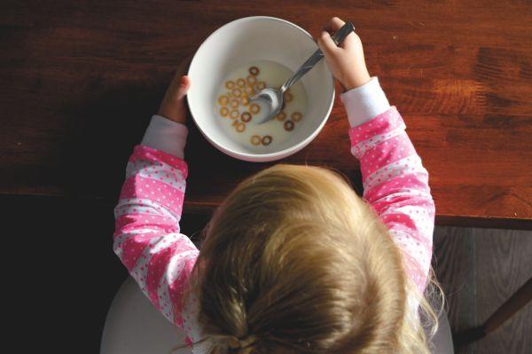 copil care mananca cereale cu lapte