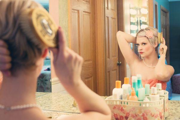 femeie care se piaptana in oglinda