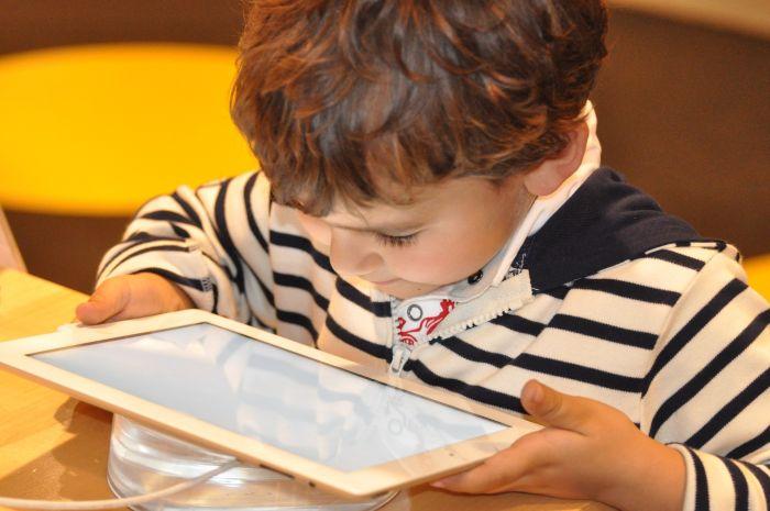 copil mic care sta in fata unei tablete si citeste