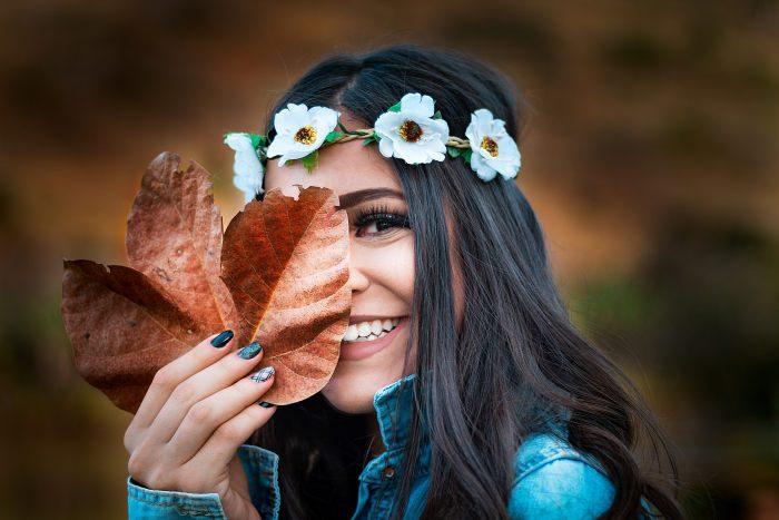 femeie cu coronita de flori albe pe cap care zambeste si isi ascunde fata dupa o frunza uscata