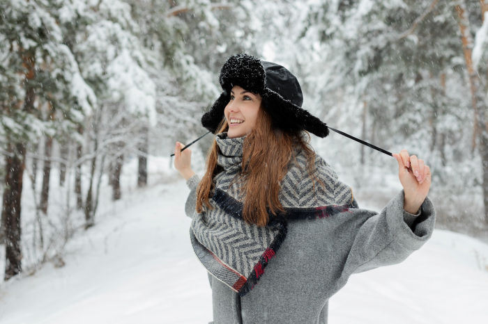 femeie imbracata cu haine groase si caciula ruseasca care rade afara in zapada