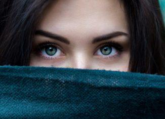 femeie cu ochi albastri si fata acoperita pe jumatate cu o esarfa albastra