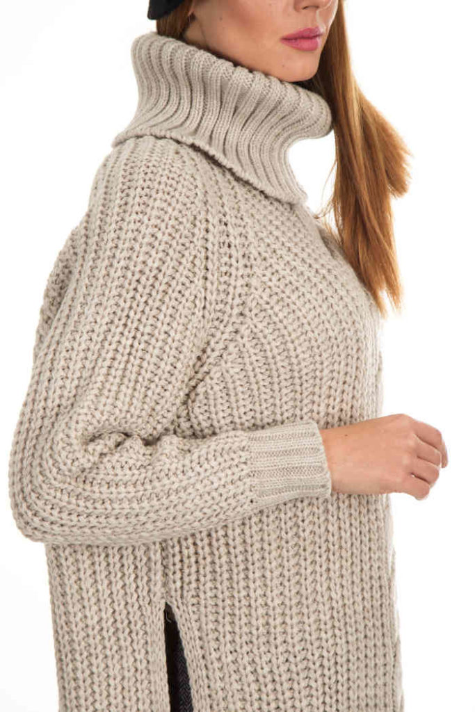 femeie blonda imbracata cu un pulover lung din lana pe gat