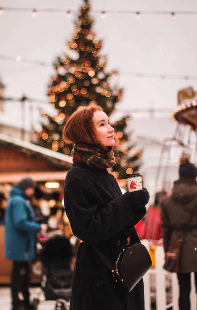 femeie imbracata de iarna cu un pahar de ceai fierbinte in mana si care se afla la un targ de craciun