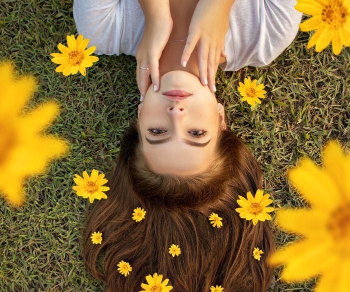 Femeie tânără care stă întinsă pe spate în iarbă și are în păr flori galbene