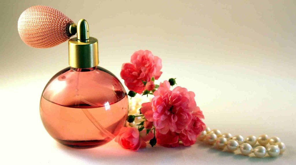Sticla cu parfum langa cativa trandafiri roz si un colier cu perle